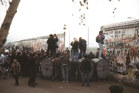 West German citizens gather at a newly created opening in the Berlin Wall