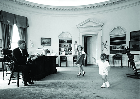 President John F. Kennedy and children play in Oval Office