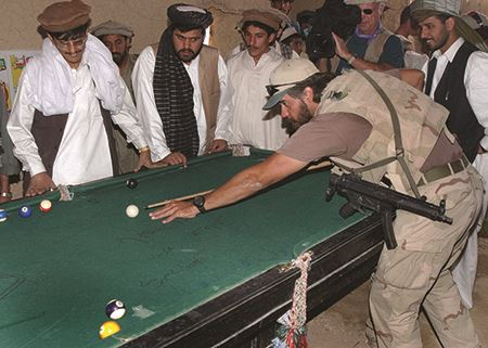 American special forces operator plays pool with men in Afghanistan