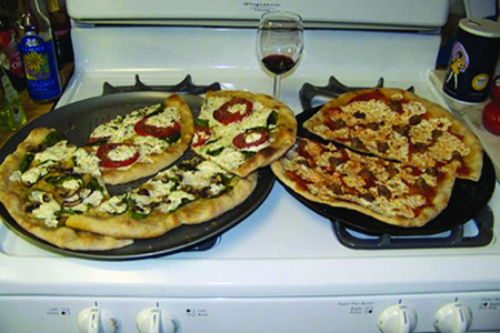 Two pizzas sitting on top of a stovetop oven